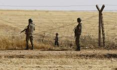 Soldados turcos fazem patrulha ao lado de pequeno menino refugiado na fronteira com a Síria Foto: Osman Orsal / REUTERS
