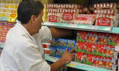 Funcionário arruma prateleira de supermercado: produtos ganharão novos rótulos a partir de domingo Foto: Fábio Guimarães / Agência O Globo