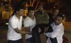 Pessoas tentam ajudar um ferido em Dhaka, após ataque em restaurante Foto: STR / AFP