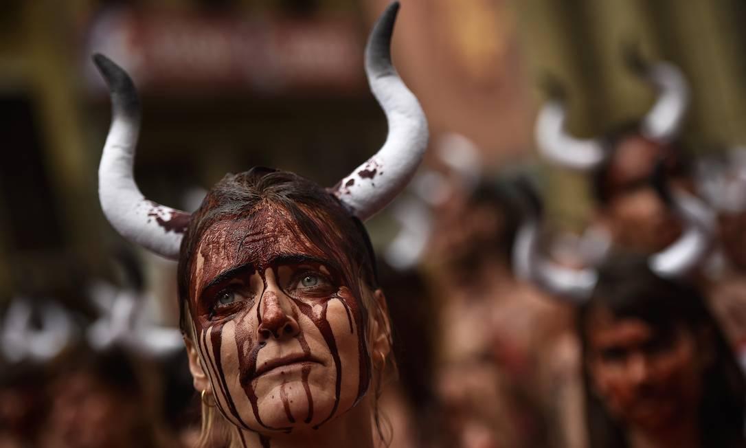 Mulher com o rosto coberto com sangue falso participa de protesto em Pamplona, no Norte da Espanha Alvaro Barrientos / AP