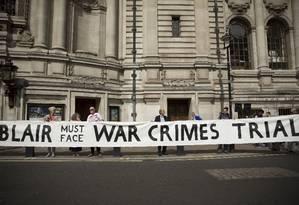 Manifestantes seguram uma grande faixa defendendo o julgamento do ex-premier Tony Blair, em frente ao Centro de Conferências Rainha Elizabeth II em Londres, pouco antes da publicação do relatório Chilcot sobre a guerra do Iraque Foto: Matt Dunham / AP