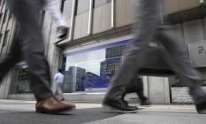 Painel eletrônico ao fundo exibe o desempenho do mercado de ações Foto: Shizuo Kambayashi / AP