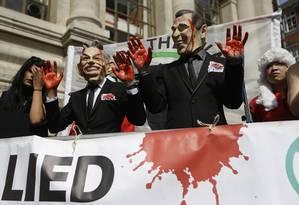 Manifestantes protestam em frente ao Centro de Conferências Rainha Elizabeth II, em Londres, vestindo uma máscara do ex-primeiro-ministro britânico Tony Blair, à esquerda, e do ex-presidente americano George W. Bush Foto: Matt Dunham / AP