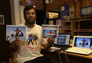 O alpinista indiano Satyarup Sidhantha, que realmente escalou o Everest, mostra fotos suas que foram alteradas pelo casal de falsificadores Foto: Bikas Das / AP