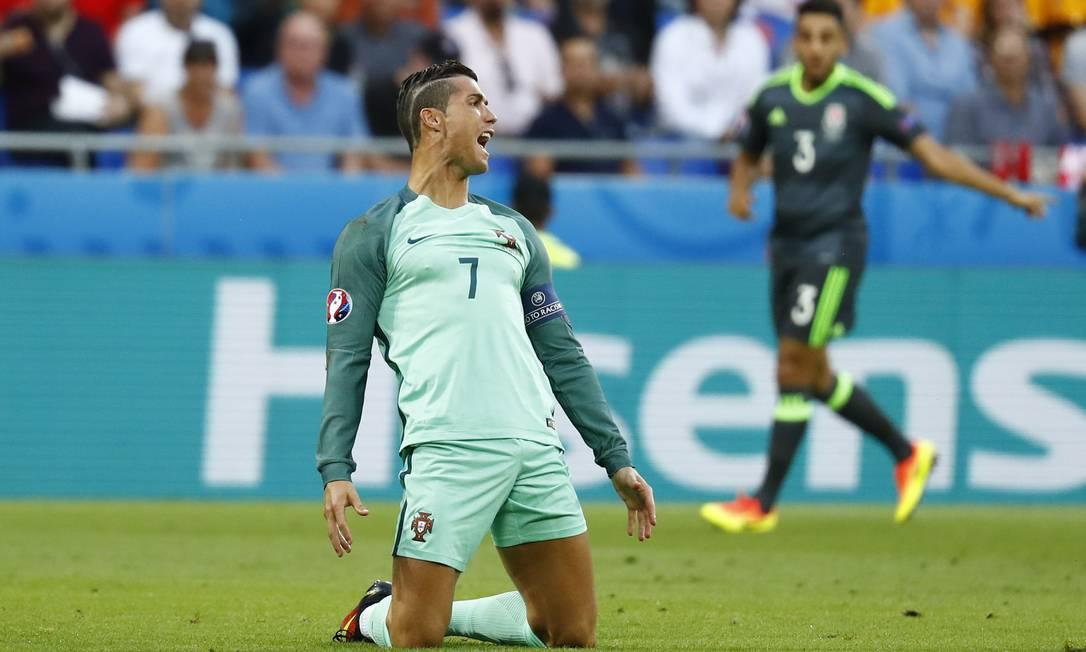 Bem ao seu estilo midiático, Cristiano Ronaldo faz pose para reclamar de falta sofrida no começo do jogo entre Portugal e País de Gales Kai Pfaffenbach / REUTERS