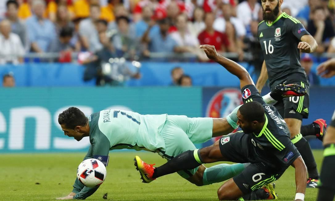 Cristiano Ronaldo é derrubado na entrada da área por Ashley Williamsno primeiro ataque de Portugal contra Gales, logo no começo da partida Kai Pfaffenbach / REUTERS