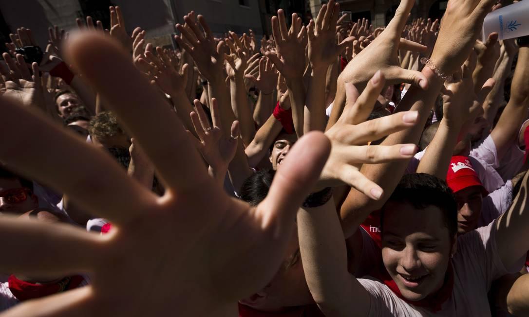 Milhares de pessoas levantam as mãos e cantam para celebrar a abertura oficial do Festival de São Firmino, em Pamplona, na Espanha Daniel Ochoa de Olza / AP