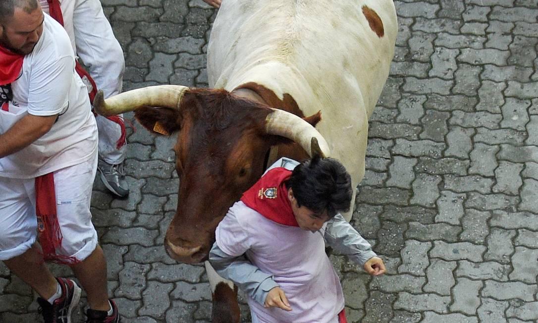 Um homem é empurrado durante a primeira corrida de touros do festival de São Firmino, em Pamplona, na Espanha ELOY ALONSO / REUTERS