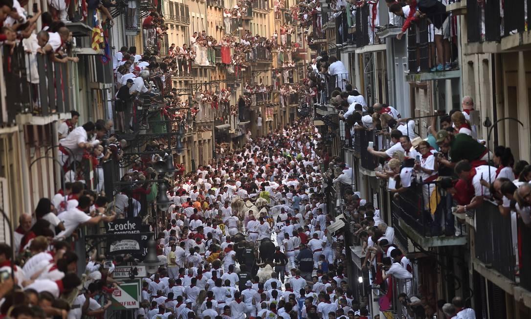 Pessoas vibram nas sacadas durante as corridas de touros do festival, que todos os anos, leva milhares de turistas à Pamplona Alvaro Barrientos / AP