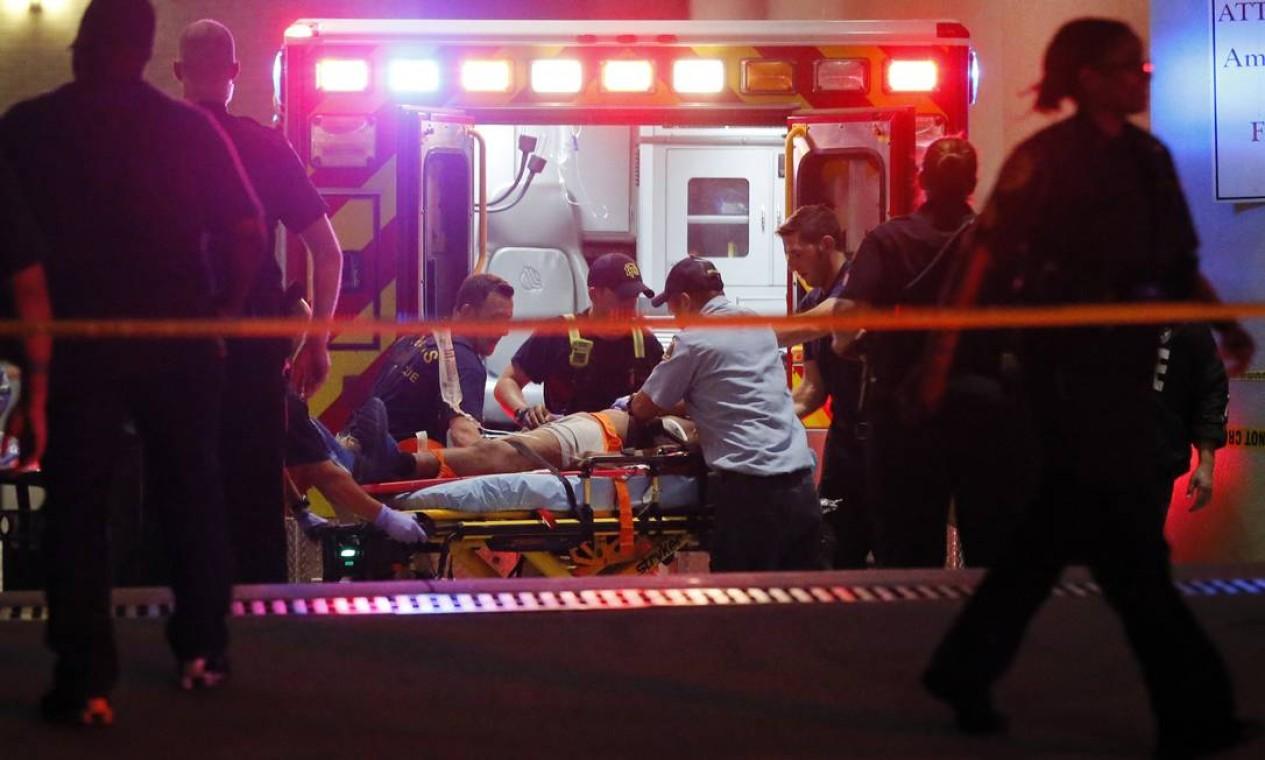Franco-atiradores matam e ferem policiais durante protesto em Dallas. Equipes de emergência socorrem uma pessoa ferida durante o ataque Foto: Tony Gutierrez / AP