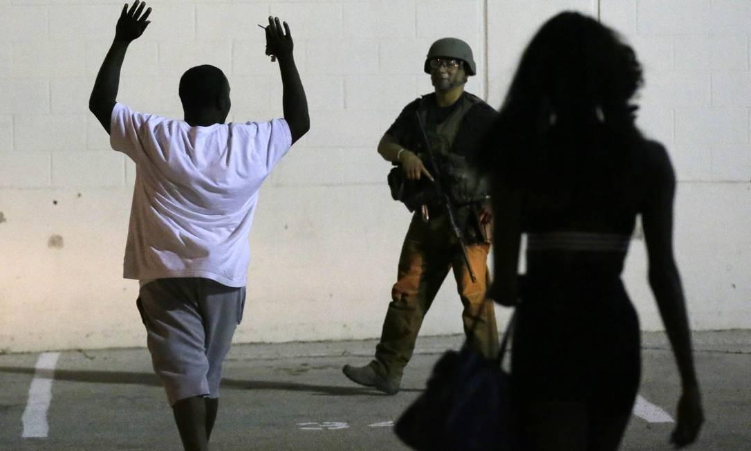 Um homem levanta as mãos enquanto é abordado por um policial Foto: LM Otero / AP