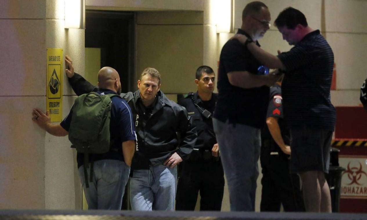 Policiais reunidos na porta do hospital aguardam notícias sobre companheiros feridos Foto: Tony Gutierrez / AP