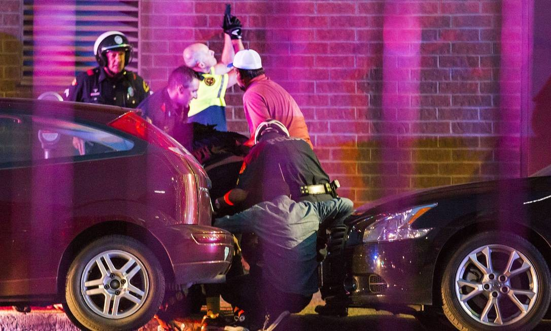 Policiais socorrem uma pessoa não identificada, ferida durante o ataque dos atiradores Foto: Smiley N. Pool / AP