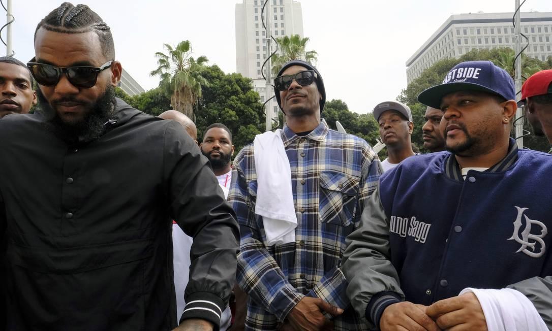 Os rappers The Game, à esquerda, e Snoop Dogg, centro, paricipam de ato de unificação e paz, do lado de fora da cerimônia de graduação de recrutas da polícia de Los Angeles Foto: RIchard Vogel / AP