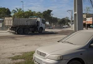 Carro estacionado próximo à rótula do Cafubá coberto por poeira: ruas por onde passam caminhões de obra ainda não têm asfalto Foto: Analice Paron / Agência O Globo