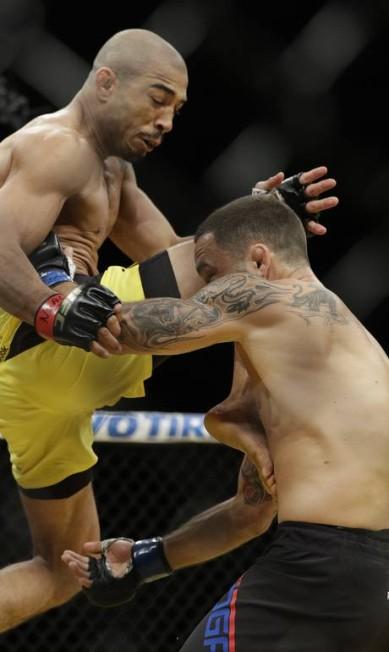 A joelhada voadora foi uma das armas de Aldo, que venceu o cinturão interino dos penas com a vitória John Locher / AP