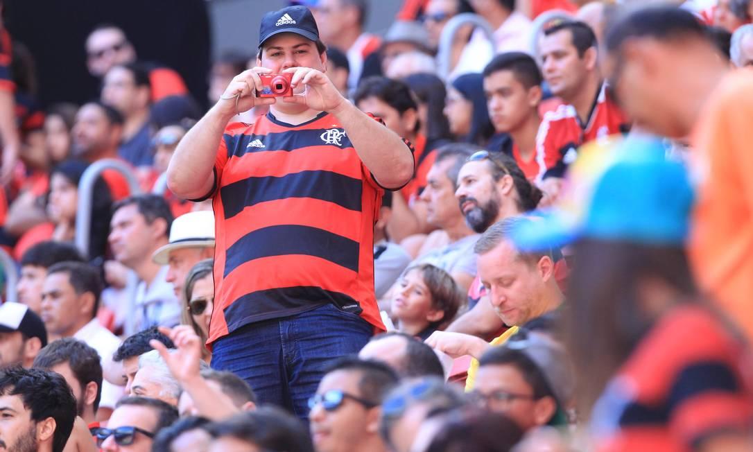 O torcedor rubro-negro se prepara para tirar uma foto na arquibancada do Estádio Mané Garrincha, em Brasília: Flamengo x Atlético-MG, pela Série A do Brasileiro Jorge William / Agência O Globo