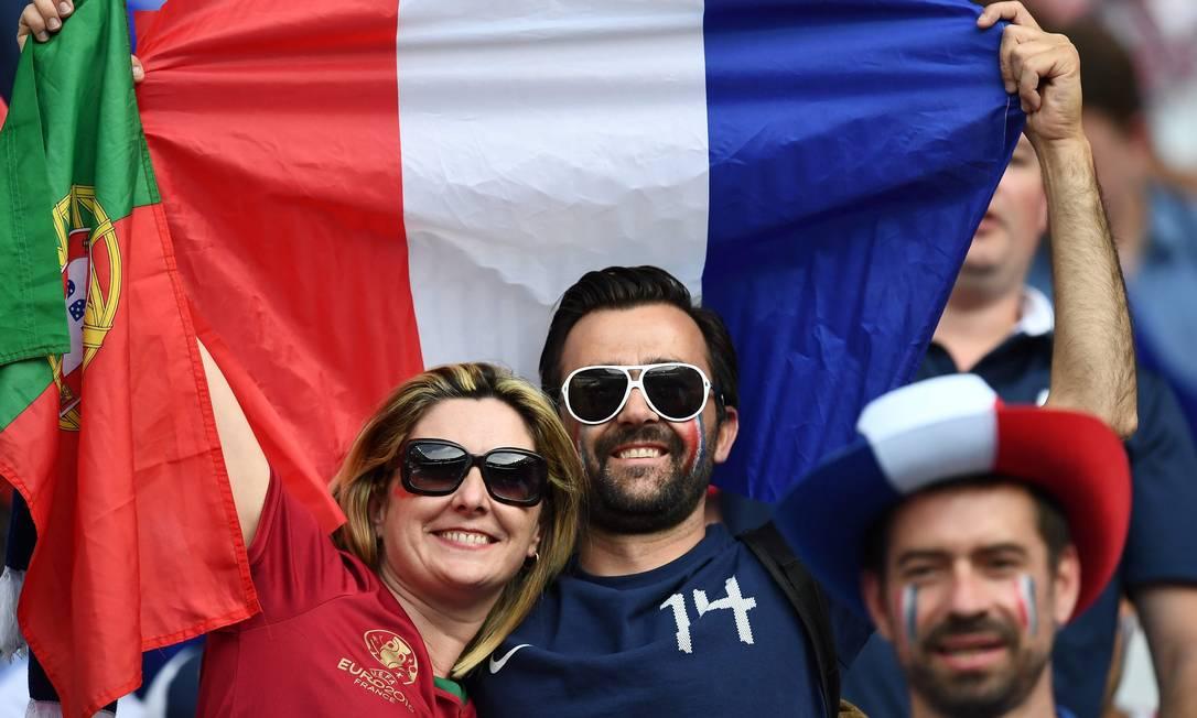 A torcedora de Portugal e o torcedor da França confraternizam bem de pertinho na arquibancada do Estádio da França, em Saint Denis FRANCK FIFE / AFP