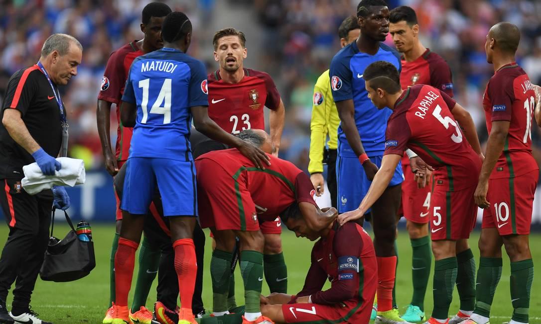 Cristiano Ronaldo fica no chão, desolado, ao ser atingido no joelho por Payet e sentir lesão que minutos depois o tirou da decisão da Eurocopa PATRIK STOLLARZ / AFP