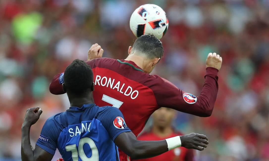 Cristiano Ronaldo cabeceia ao se antecipar a Sagna no duelo entre portugueses e franceses na final da Euro VALERY HACHE / AFP