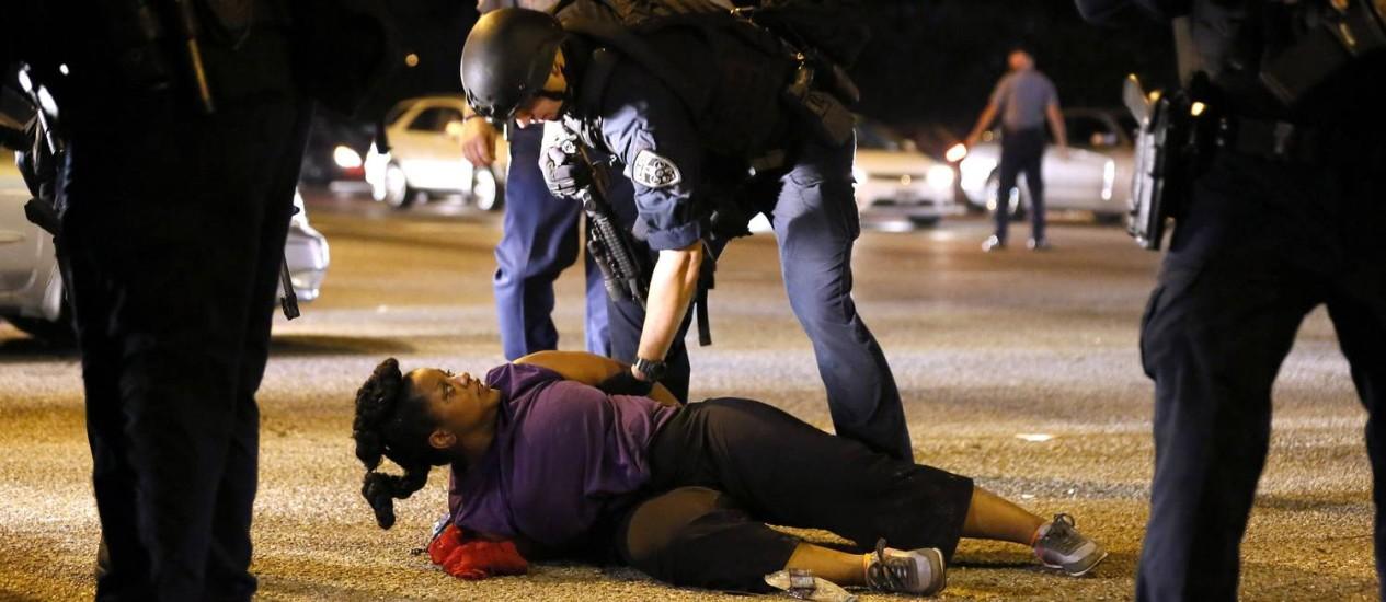 Uma mulher negra é detida, algemada e presa por um policial branco: ela estava entre os manifestantes que nprotestavam do lado de fora do quarte-general da polícia de Baton Rouge, capital da Louisiana Foto: JONATHAN BACHMAN / REUTERS