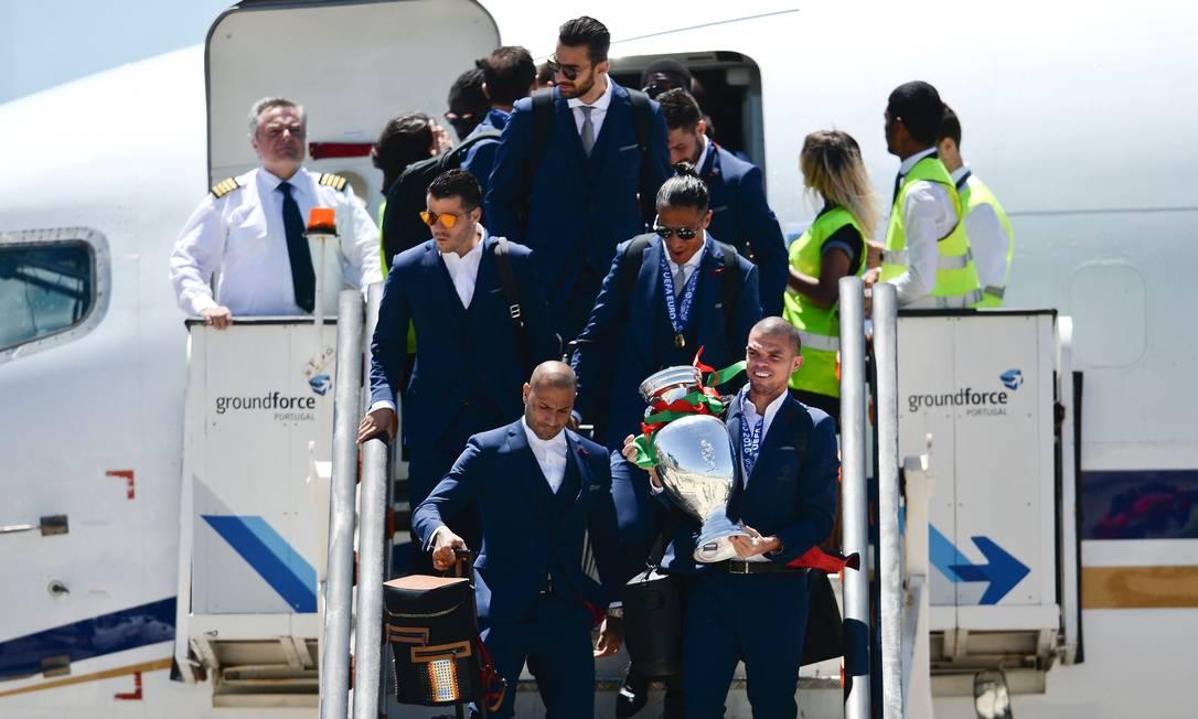 Um dos melhores jogadores portugueses no torneio, o zagueiro Pepe desce do avião com o troféu de campeão PATRICIA DE MELO MOREIRA / AFP