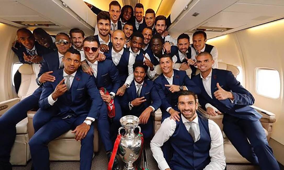 Antes do desembarque, o time fez uma foto dentro do avião com a taça FRANCISCO PARAISO / AFP