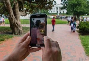 Mulher busca pokémons em parque próximo à Casa Branca, em Washington Foto: JIM WATSON / AFP