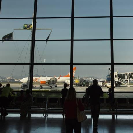 Aeroporto Santos Dumont: passageiros observam a movimentação dos aviões no saguão Foto: ANTONIO SCORZA / Agência O Globo