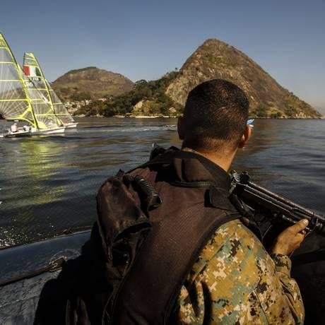 Num bote, agente da Polícia Ambiental patrulha a Enseada de Jurujuba enquanto velejadores da delegação italiana treinam: rondas na Baía de Guanabara começaram na terça-feira Foto: Guilherme Leporace / Agência O Globo