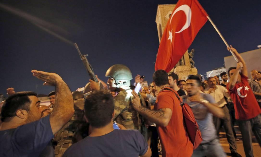 Partidários do presidente turco Recep Tayyip Erdogan protestam em frente aos soldados na Praça Taksim Foto: Emrah Gurel / AP