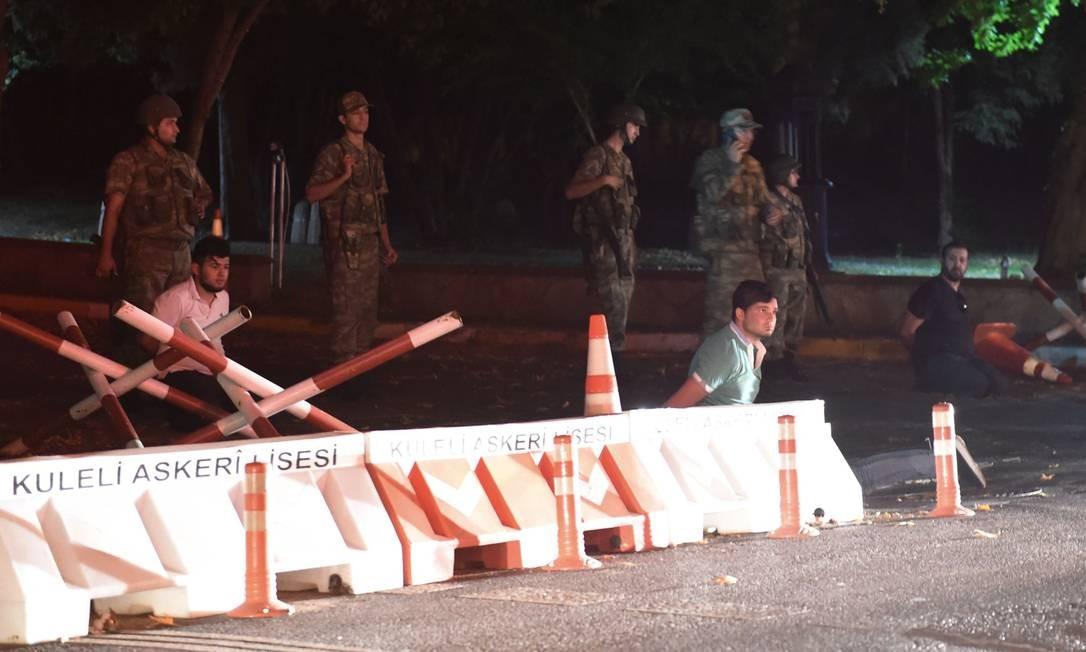 Forças de segurança turcas detêm indivíduos não identificados ao lado de um dos bloqueios às pontes sobre o Bósforo Foto: BULENT KILIC / AFP