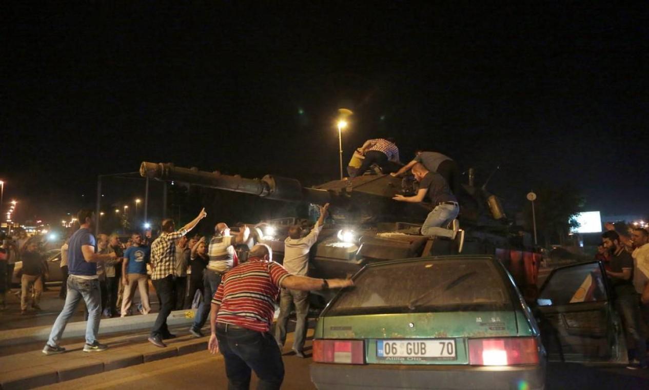 Pessoas avançam sobre um tanque que toma posição em uma rua de Ancara Foto: Burhan Ozbilici / AP