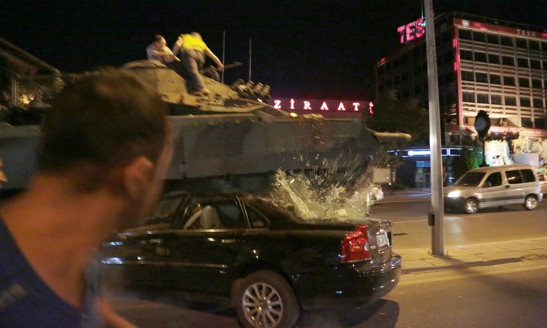 Tanque esmaga um carro enquanto defensores do governo tentam impedir a ação Foto: Burhan Ozbilici / AP