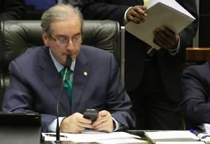 O deputado afastado Eduardo Cunha (PMDB-RJ) com o celular na cadeira da presidência da Câmara, em março, antes de ser afastado pelo Supremo Tribunal Federal Foto: Ailton de Freitas / Agência O Globo / 5-3-2015