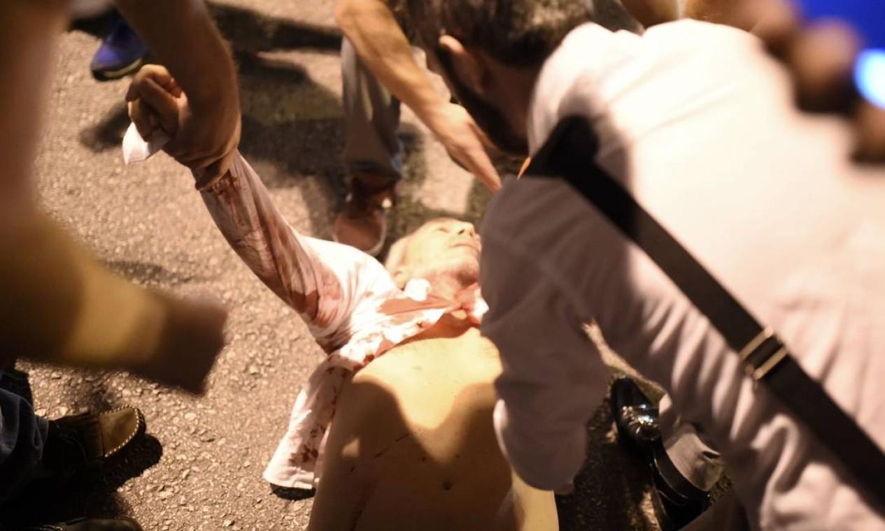 Pessoas socorrem um homem atingido por tiro disparado por soldados turcos Foto: BULENT KILIC / AFP
