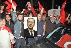 Apoiadores do presidente Recep Tayyip Erdogan protestam em frente ao consulado turco em Stuttgart, Alemanha Foto: Andreas Rosar / AP