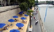 Praia artificial às margens do Rio Sena, parte do projeto Paris Plages Foto: Bertrand Guay / AFP