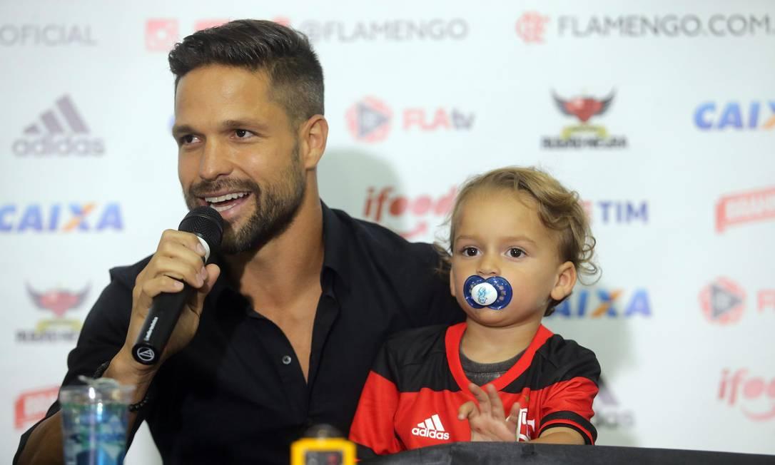 Diego fala com a imprensa com o filho caçula, Matteo, no colo Rafael Moraes