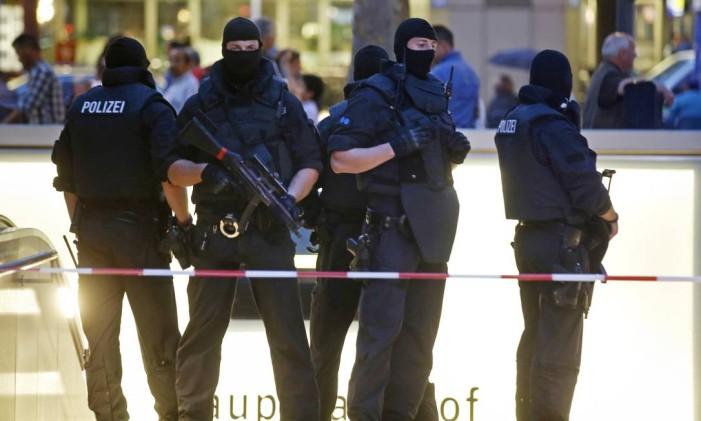 Policiais montam guarda na entrada de uma estação de trem, nas imediações do shopping Olympia, em Munique Foto: MICHAEL DALDER / REUTERS