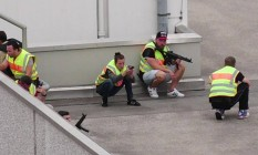Confusão. Policiais se abrigam no estacionamento do shopping, em busca de atiradores: ataque em Munique volta a abalar a imagem da líder alemã Foto: HANDOUT / REUTERS