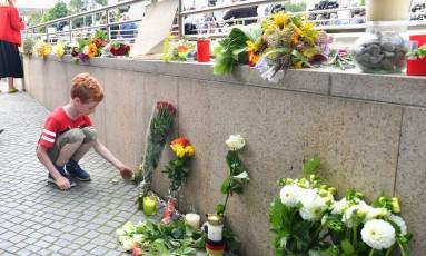 Um menino deixa flores perto de um shopping onde um atirador matou nove pessoas em Munique, na Alemanha Foto: Kerstin Joensson / AP