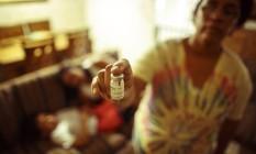 Adriana Coelho segura um frasco do remédio que precisa dar para o neto Christian, de 8 anos, portador de uma doença que ataca a produção de enzimas: tratamento, conseguido na Justiça, custa R$ 22 mil por mês Foto: Agência O Globo / Daniel Marenco