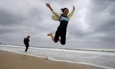 A chinesa Feng Lian diverte-se na Praia de Copacabana: ela chegou ao Rio com um grupo de 20 pessoas, que contratou segurança particular Foto: Domingos Peixoto / Agência O Globo