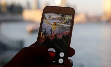 Jogador visualiza pokémon em seu celular Foto: Kin Cheung / AP