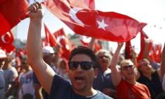 Turcos levam bandeiras à praça Taksim, em Istambul, em protesto pela democracia Foto: OSMAN ORSAL / REUTERS