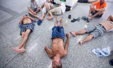Chineses se refrescam em frente ao ar condicionado de uma estação de metrô em Hangzhou, onde as temperaturas estão acima dos 40º Celsius Foto: AP
