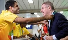 Presidente do COI, Thomas Bach, recebe a credencial de um volunário, ao chegar no aeroporto internacional do Rio Foto: POOL / REUTERS