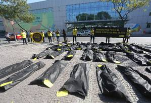 Protesto da Anistia Internacional em frente ao Comitê Olímpico Brasileiro. Na foto, sacos representando os mortos pela PM Foto: Custódio Coimbra / Agência O Globo