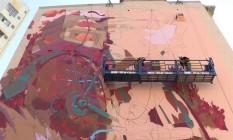 Ciclismo: o grafiteiro Thiago Molon enche de vermelho a lateral de um prédio na Praça da Bandeira Foto: Ana Beatriz Marin / Agência O Globo